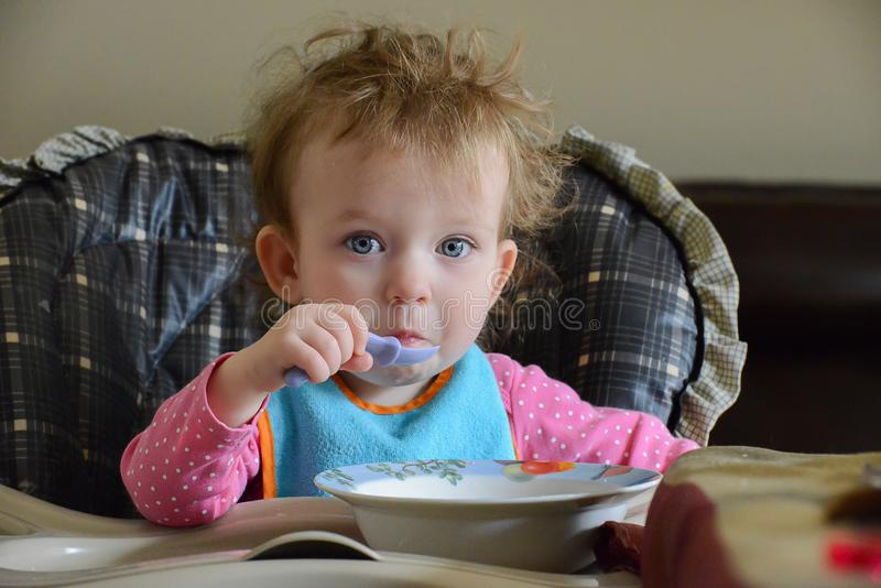 Adorable Caucasian baby sits on the table, holds a spoon and eats. Baby is very surprised. Infant`s hear is not combed. stock photography