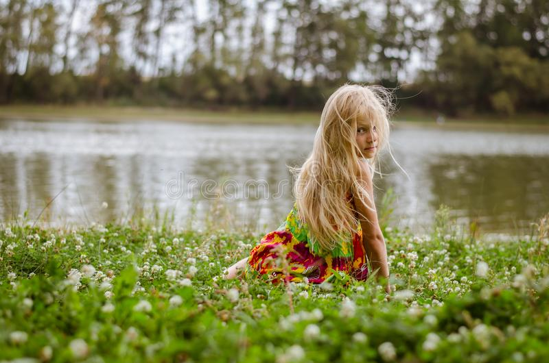 Sad girl sitting alone in the grass by the river royalty free stock photography