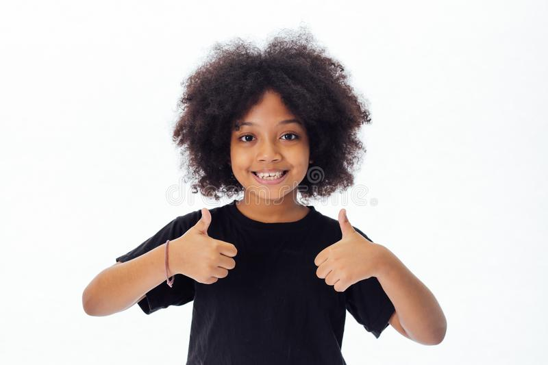 Adorable and cheerful African American kid with afro hairstyle giving thumbs up. Isolated over white background stock photo