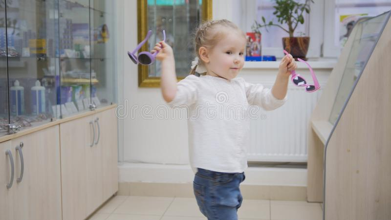 Adorable child blonde girl in ophthalmology clinic plays in hall near glasses store. Close up stock photography
