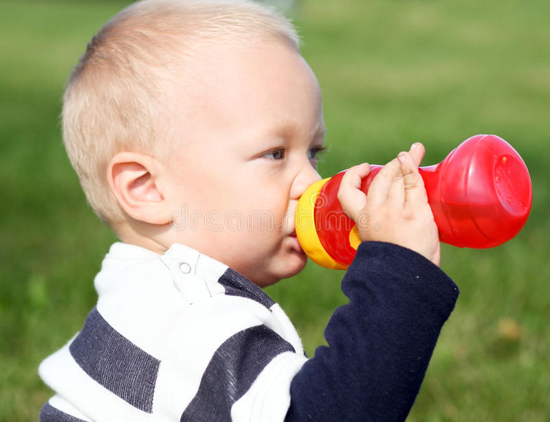 Adorable child drinking stock photos
