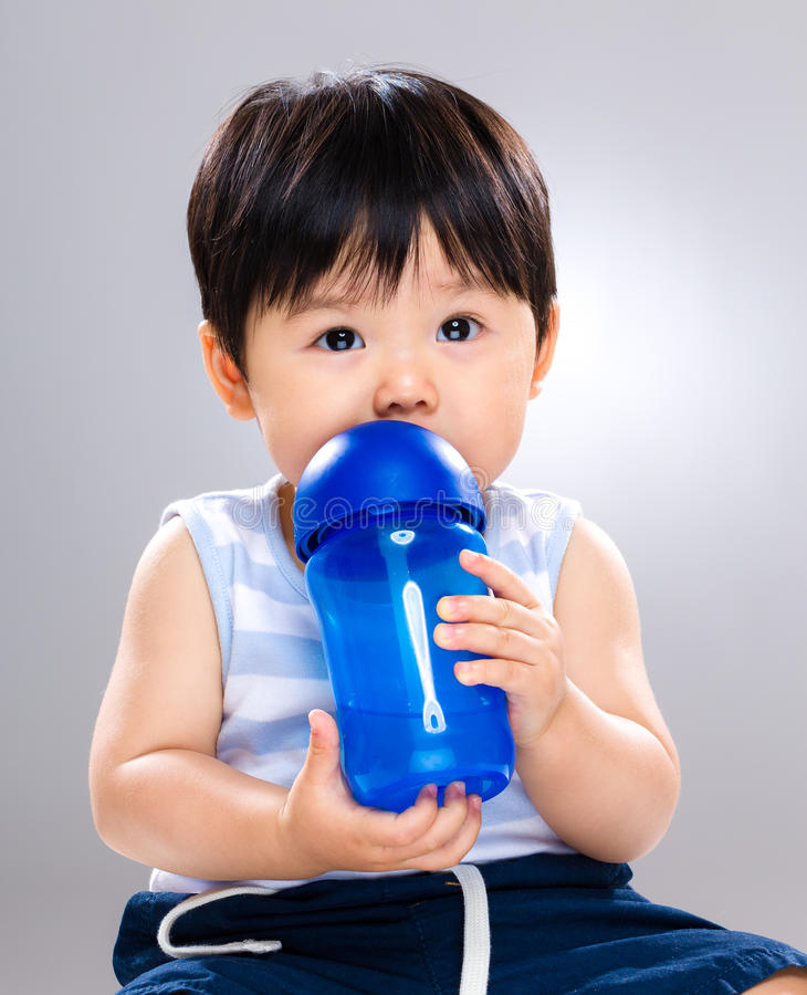 Adorable child drinking from bottle royalty free stock photo