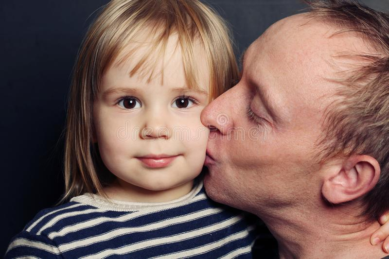 Adorable child and father. Dad kissing her baby, loving family royalty free stock image