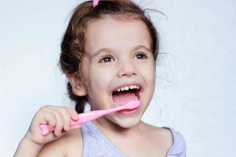 Adorable child girl cleaning teath by toothbrush. royalty free stock photography