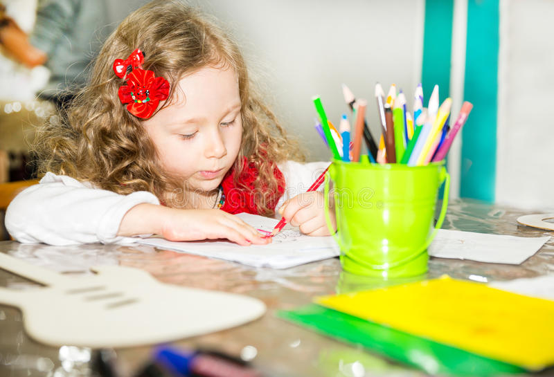 Adorable child girl drawing with colorful pencils in nursery room. Kid in kindergarten in Montessori preschool class. Adorable child girl drawing with colorful stock photo