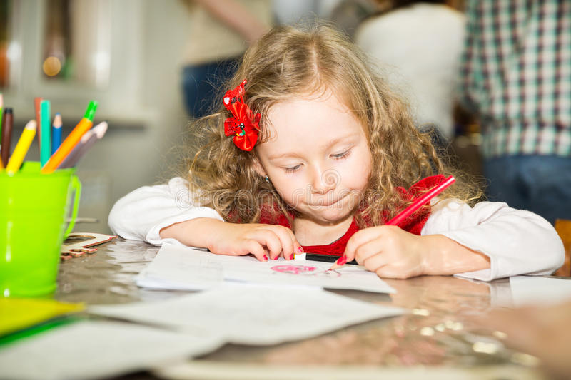 Adorable child girl drawing with colorful pencils in nursery room. Kid in kindergarten in Montessori preschool class. Adorable child girl drawing with colorful royalty free stock photography