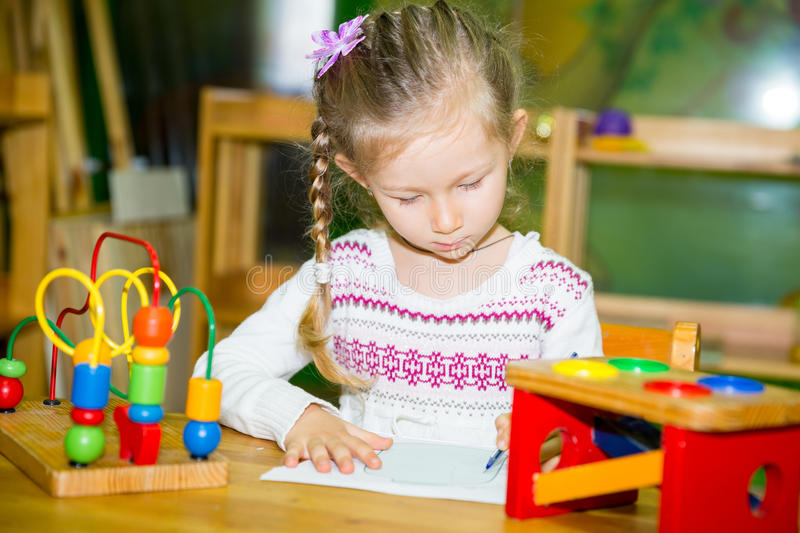 Adorable child girl drawing with colorful pencils in nursery room. Kid in kindergarten in Montessori preschool class. Adorable child girl drawing with colorful royalty free stock image