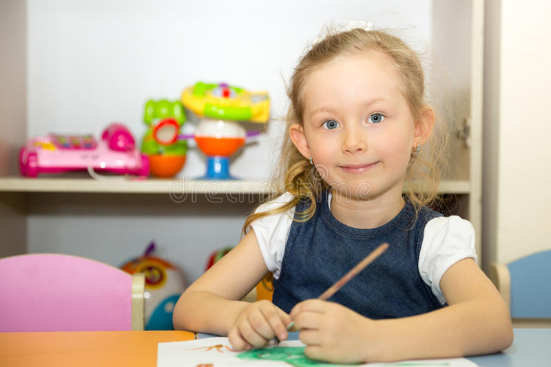 Adorable child girl draws a brush and paints in nursery room. Kid in kindergarten in Montessori preschool class. Adorable child girl draws a brush and paints in royalty free stock photo