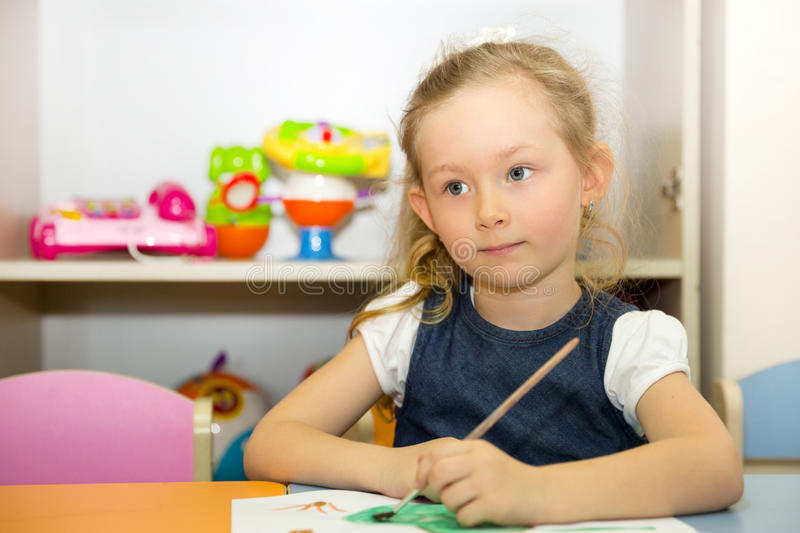 Adorable child girl draws a brush and paints in nursery room. Kid in kindergarten in Montessori preschool class. Adorable child girl draws a brush and paints in royalty free stock image