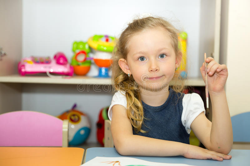 Adorable child girl draws a brush and paints in nursery room. Kid in kindergarten in Montessori preschool class. Adorable child girl draws a brush and paints in stock photo