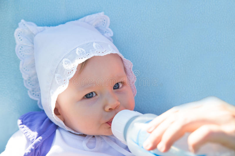 Adorable child girl with infant formula in bottle drinking milk royalty free stock photography