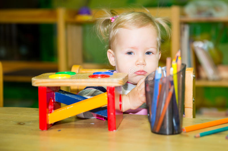 Adorable child girl playing with educational toys in nursery room. Kid in kindergarten in Montessori preschool class. royalty free stock photos