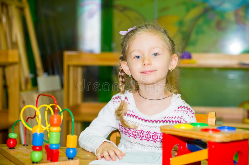 Adorable child girl playing with educational toys in nursery room. Kid in kindergarten in Montessori preschool class. Adorable child girl playing with stock photos