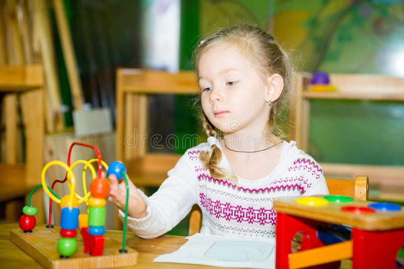 Adorable child girl playing with educational toys in nursery room. Kid in kindergarten in Montessori preschool class. Adorable child girl playing with stock images