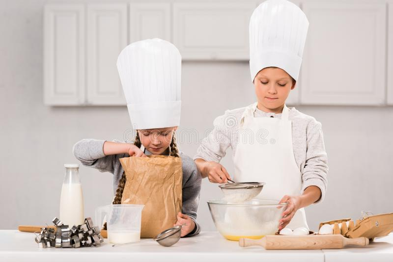 Adorable children in aprons and chef hats during food preparation at table. In kitchen royalty free stock images