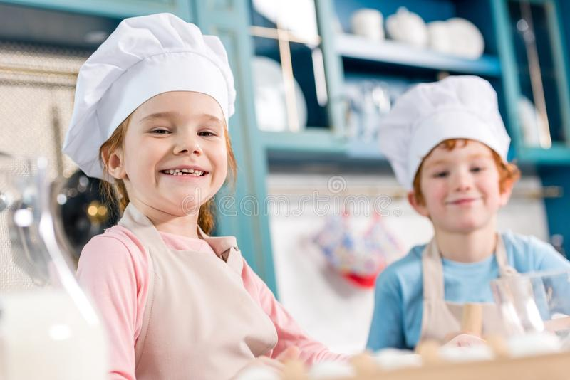 Adorable children in chef hats and aprons smiling at camera while cooking together. In kitchen stock photo