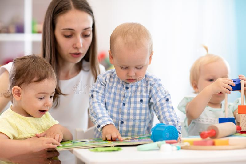 Young children learning book with their teacher, Nursery babies on lesson. Kids and mentor in kindergarten royalty free stock photo