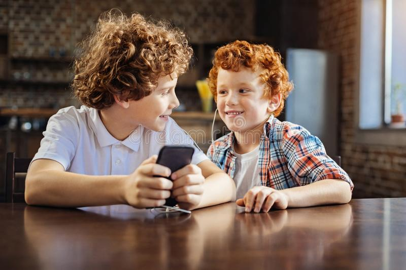 Adorable children listening to music on smartphone. Do you like this one. Relaxed little brothers chatting and smiling while both sitting at a table and royalty free stock photos