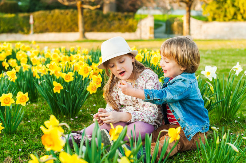 Adorable children. Playing with flowers on a nice sunny spring day stock photos