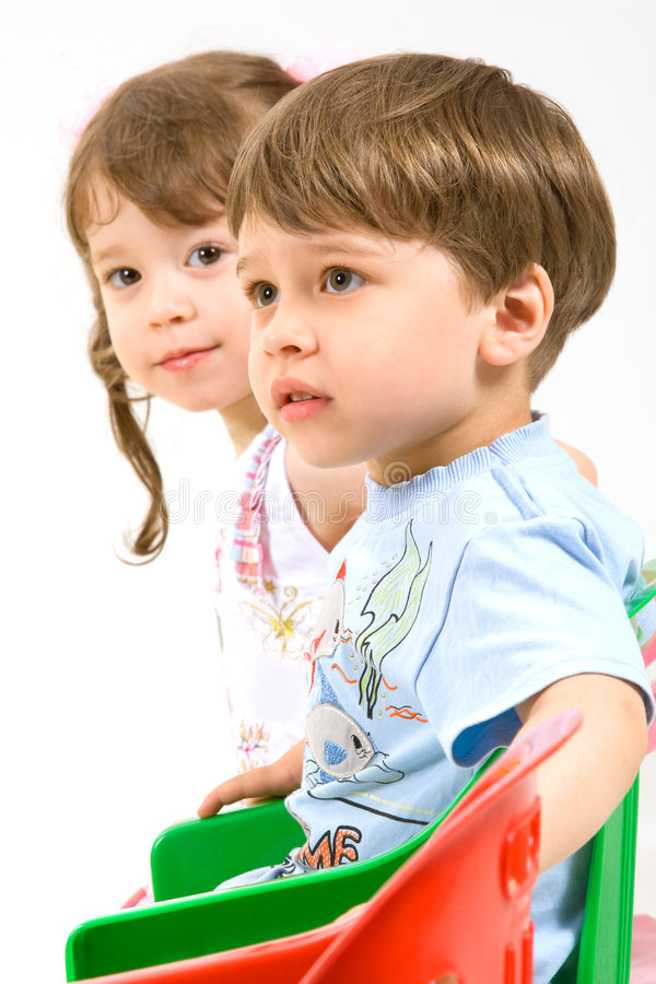 Adorable children sitting on colorful chairs stock photography