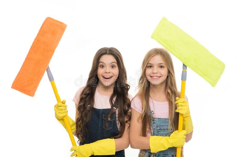 Adorable clean freaks. Cute girls holding mops for cleaning floor. Small cleaning ladies. Little cleaners with modern royalty free stock photography