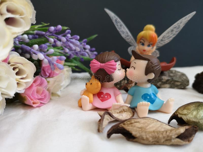 Closeup and macro shot of miniature kissing babies in the garden while fairy Tinkerbell stalking behind.. royalty free stock photography