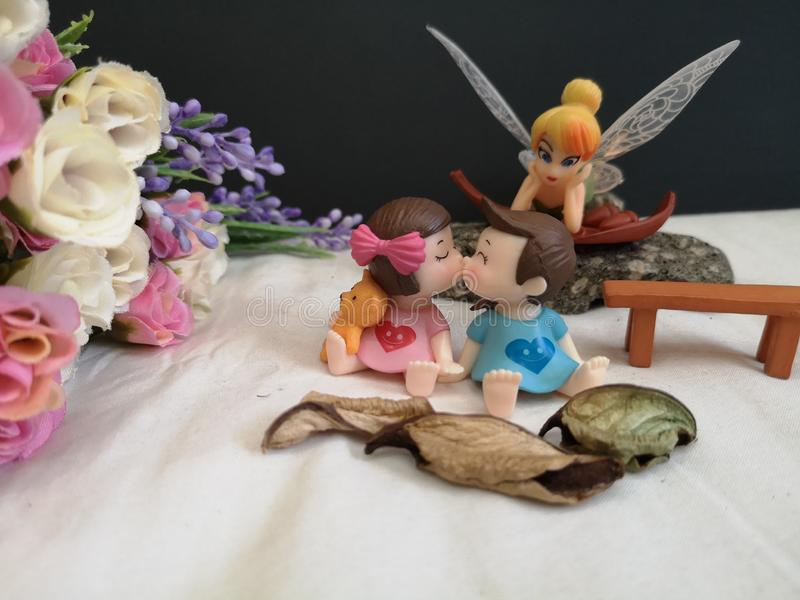 Closeup and macro shot of miniature kissing babies in the garden while fairy Tinkerbell stalking behind.. stock image