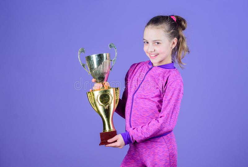 Adorable cup winner. Small girl holding silver cup. Little child with cup shaped sports trophy. Cute athlete being stock images