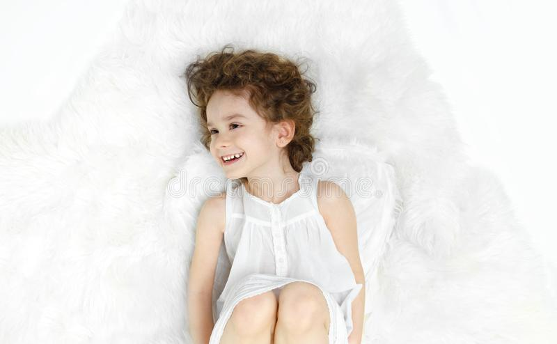 Adorable curly little girl lying down on fur, looking at a side, in white dress and wings, isolated on white background. stock photography