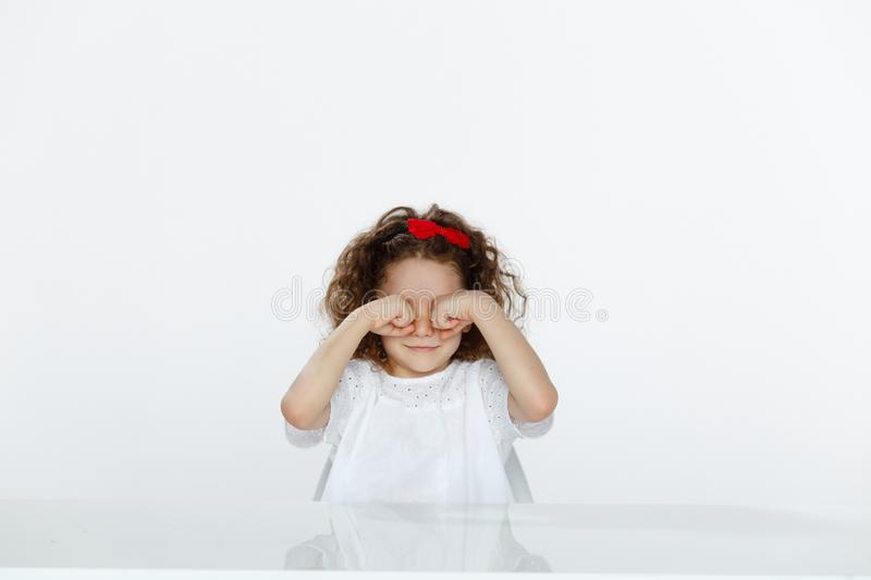 Adorable curly little girl in studio, seated at a table, rubbing his eyes with hands, isolated on a white backgrounds. stock images
