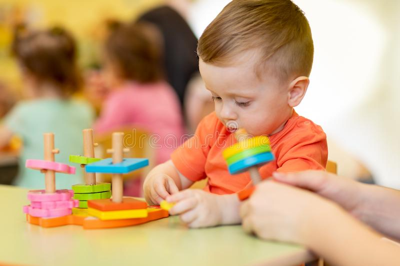 Adorable cute baby boy plays with educational sorter toys at kindergarten or nursery. Healthy happy toddler child royalty free stock image