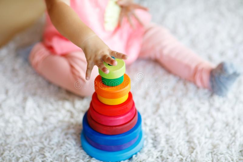 Adorable cute beautiful little baby girl playing with educational colorful wooden rainboy toy pyramid royalty free stock images
