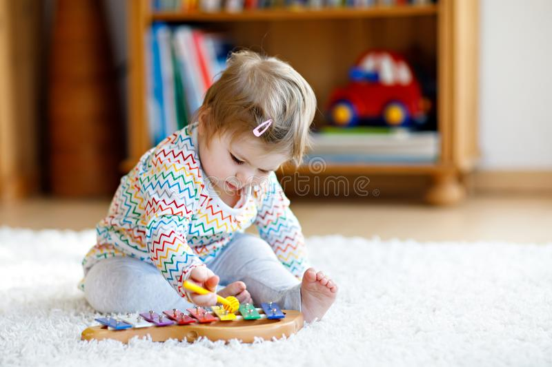 Adorable cute beautiful little baby girl playing with educational wooden music toys at home or nursery. Toddler with royalty free stock image