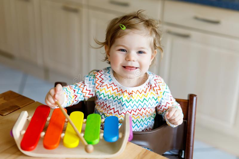 Adorable cute beautiful little baby girl playing with educational wooden music toys at home or nursery stock photo