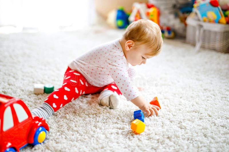 Adorable cute beautiful little baby girl playing with educational wooden toys at home or nursery. Healthy happy toddler. With colorful red car indoors. child stock image