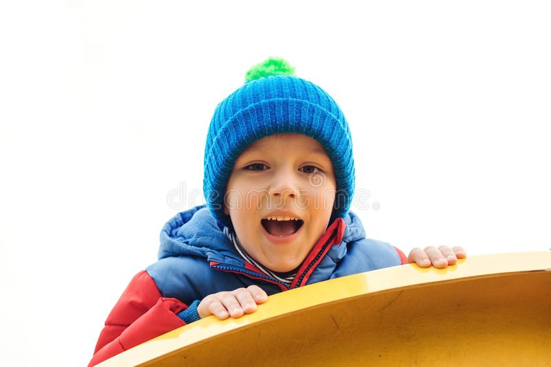 Adorable cute boy playing on playground on a cold day. Child wearing funny hat and red jacket. Funny little boy outdoors. Kids out royalty free stock photos