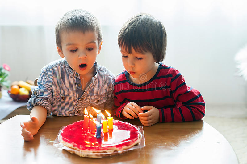 Adorable cute boys, blowing candles on a birthday cake. At home stock photos