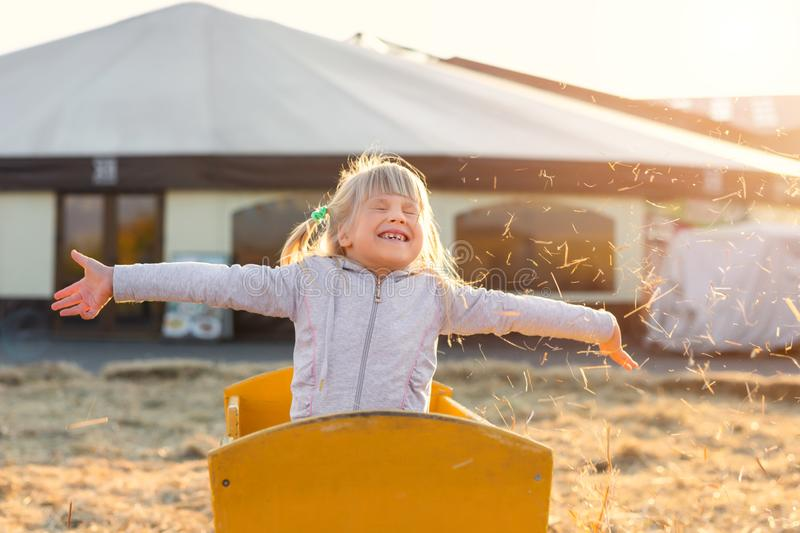 Adorable cute caucasian blond kid girl sitting in wooden cart having fun throwing straw or hay at farm or park during warm autumn. Evening. Happy childhood stock photo