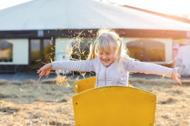 Adorable cute caucasian blond kid girl sitting in wooden cart having fun throwing straw or hay at farm or park during warm autumn. Evening. Happy childhood stock photography