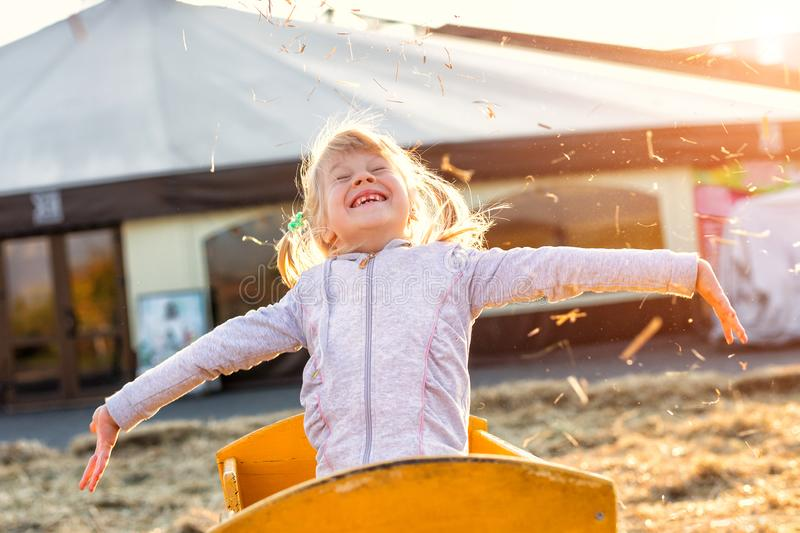 Adorable cute caucasian blond kid girl sitting in wooden cart having fun throwing straw or hay at farm or park during warm autumn. Evening. Happy childhood royalty free stock photo