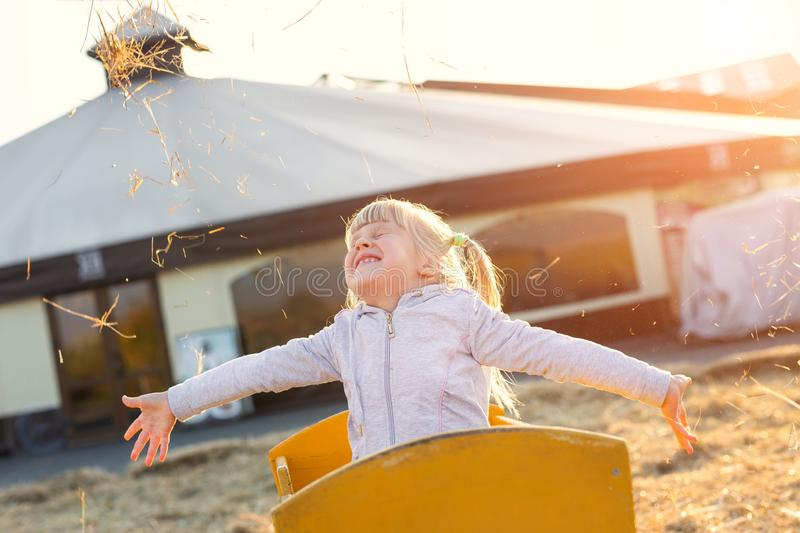 Adorable cute caucasian blond kid girl sitting in wooden cart having fun throwing straw or hay at farm or park during warm autumn. Evening. Happy childhood royalty free stock images