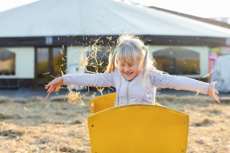 Adorable cute caucasian blond kid girl sitting in wooden cart having fun throwing straw or hay at farm or park during warm autumn. Evening. Happy childhood stock image