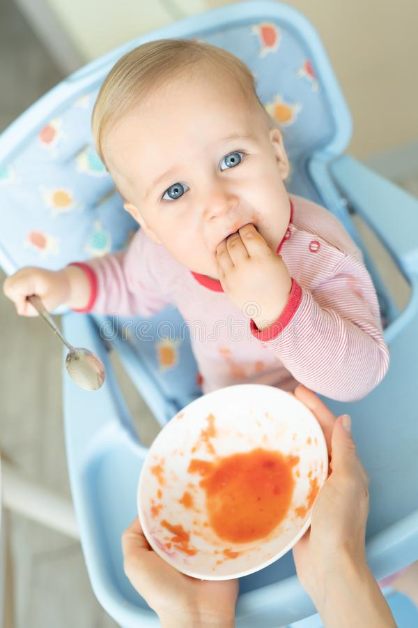 Adorable cute caucasian blond toddler boy eating tasty vegetable soup in chair at kithcen indoor. Mother feeding baby healthy food. With spoon. Natural children royalty free stock photos