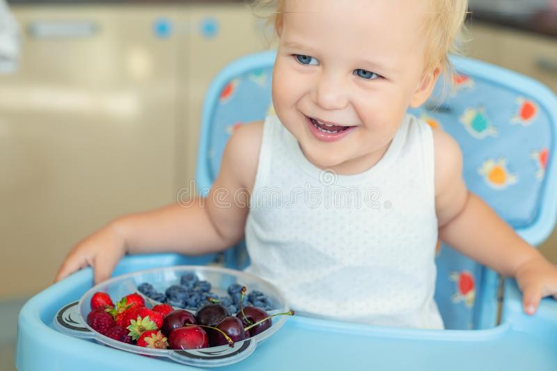 Adorable cute caucasian blond toddler boy enjoy tasting different seasonal fresh ripe organic berries sitting in highchair at home. Kitchen. Happy kid eating royalty free stock photography