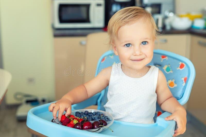 Adorable cute caucasian blond toddler boy enjoy tasting different seasonal fresh ripe organic berries sitting in highchair at home. Kitchen. Happy kid eating stock photo