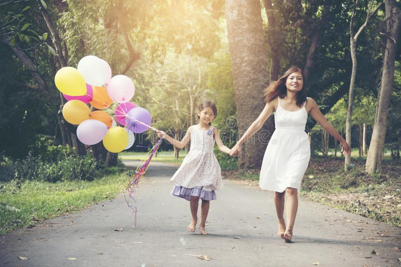 Adorable cute girl holding balloons with mother walking on the road in the park royalty free stock photography