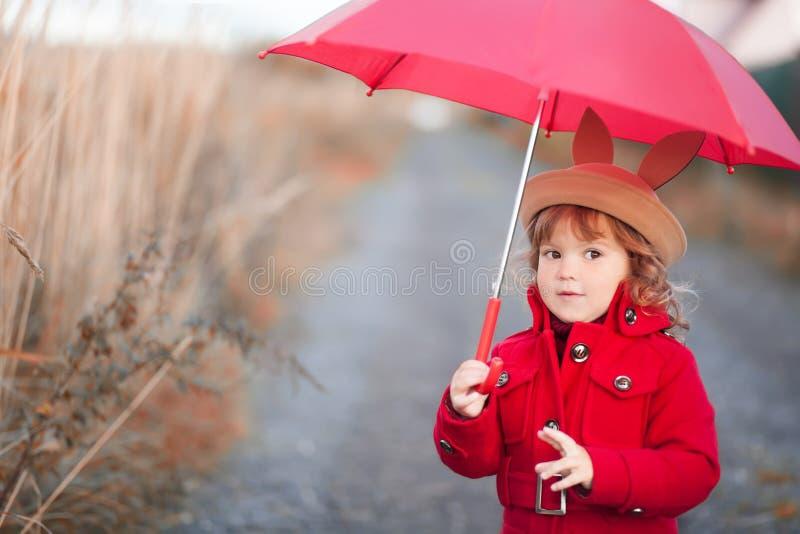 Little girl walking with umbrella, autumn day. stock photos