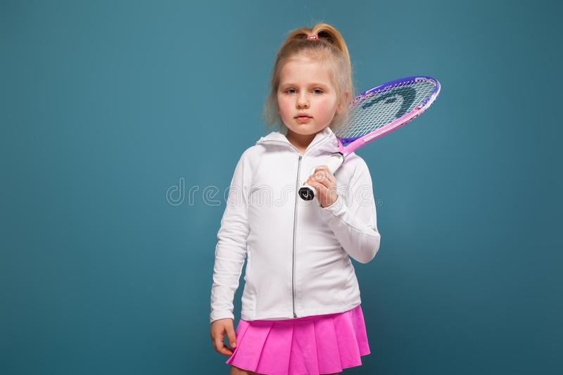 Adorable cute little girl in white shirt, white jacket and pink skirt with tennis racket royalty free stock photos