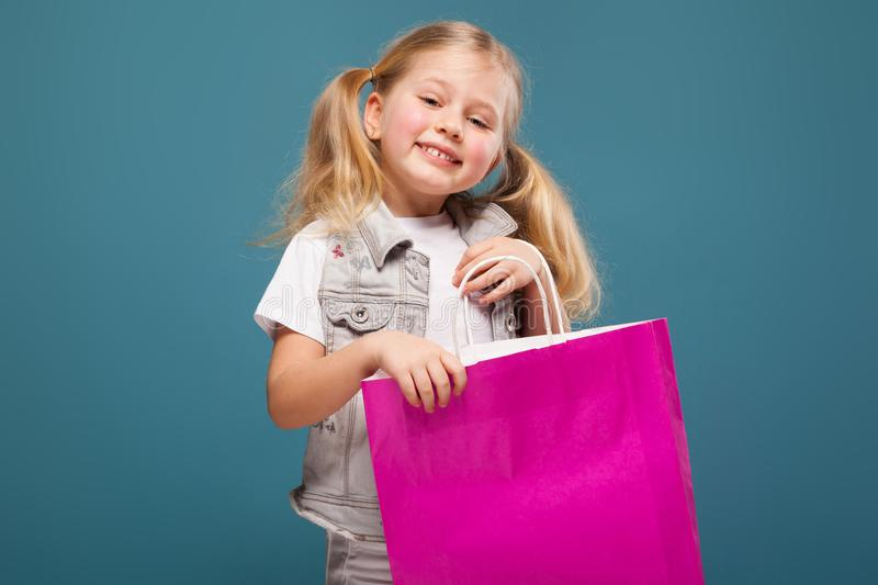 Adorable cute little girl in white shirt, white jacket and white trousers hold purple paper bag stock photography