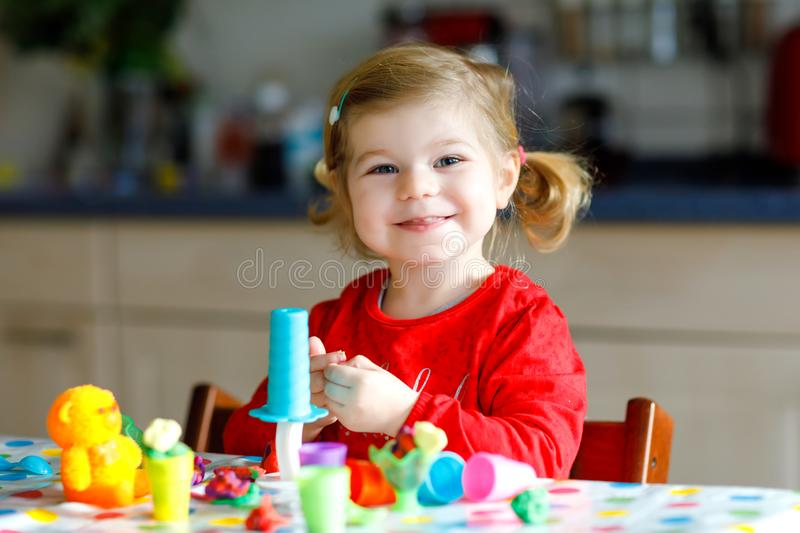 Adorable cute little toddler girl with colorful clay. Healthy baby child playing and creating toys from play dough stock image